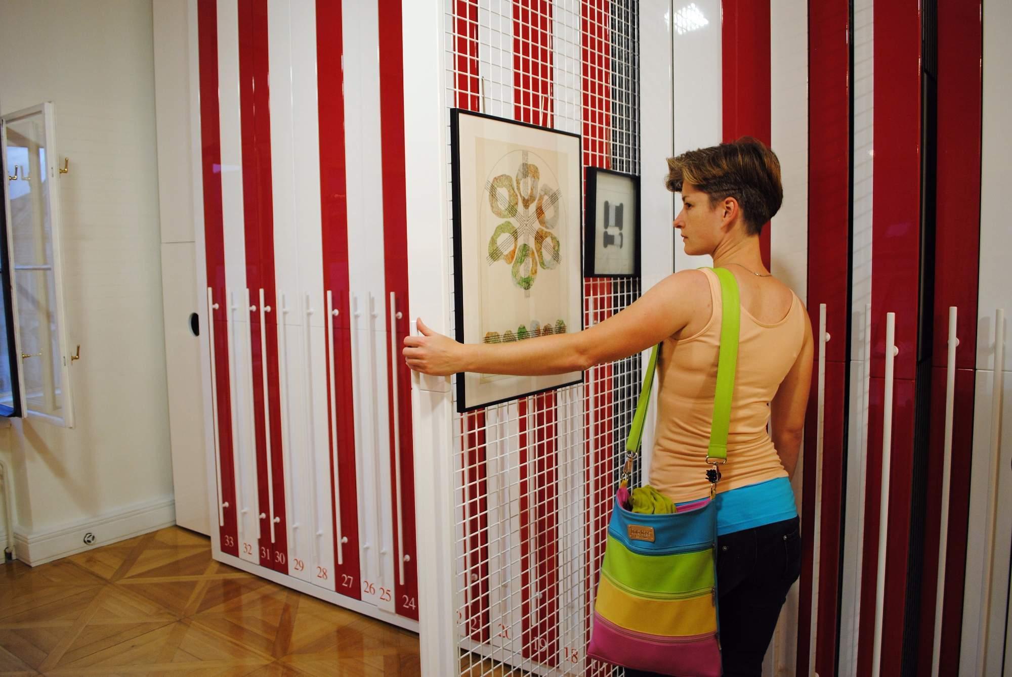 Návštěvnice si prohlíží, jaké obrazy jsou v nabídce. Foto: Barbora Ficbauerová