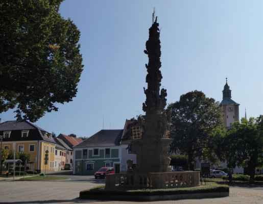 Hoštka, odsud pojedeme autobusem do Radouně. Náměstí s morovým sloupem a věž kostela sv. Otmara