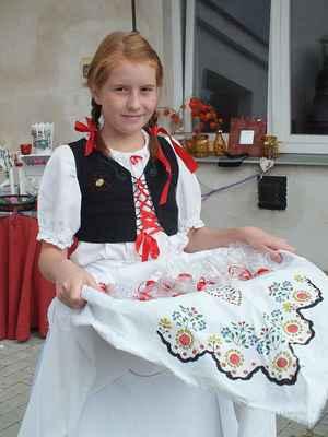 Děvčica z národopisného souboru Borověnka v dobovém kroji.