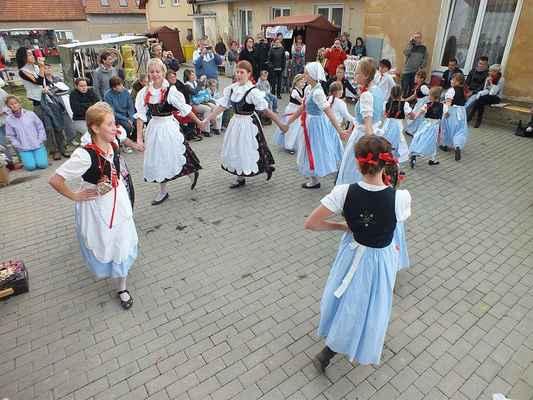 Děti tančí a zpívají.