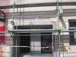 Dříve tady býval průchod, později velké prosklené dvoukřídlé dveře a od roku 2018 tady budou dva samostatné vchody. Velká rekonstrukce budovy, v které se nachází i restaurace BARON, má trvat do konce dubna 2018.