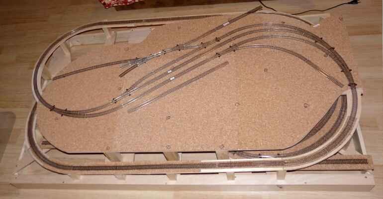 Konstrukce - Zkušební a následně finální položení kolejí. Chybí kolej vlečky, ta byla doplněna později.