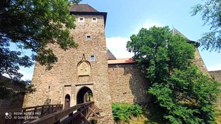 vstupní brána do hradu - Hrad byl založen na počátku 14. století. Postupem času byl rozšířen a změnil mnoho majitelů. Během té doby byl několikrát obléhán. Ke konci 18. století upadl vojenský význam hradu a byl opuštěn. Dnes můžeme obdivovat jeden z největších hradních komplexů u nás. Dochovaly se mohutné hradební zdi, několik věží, pět bran, věže a paláce.